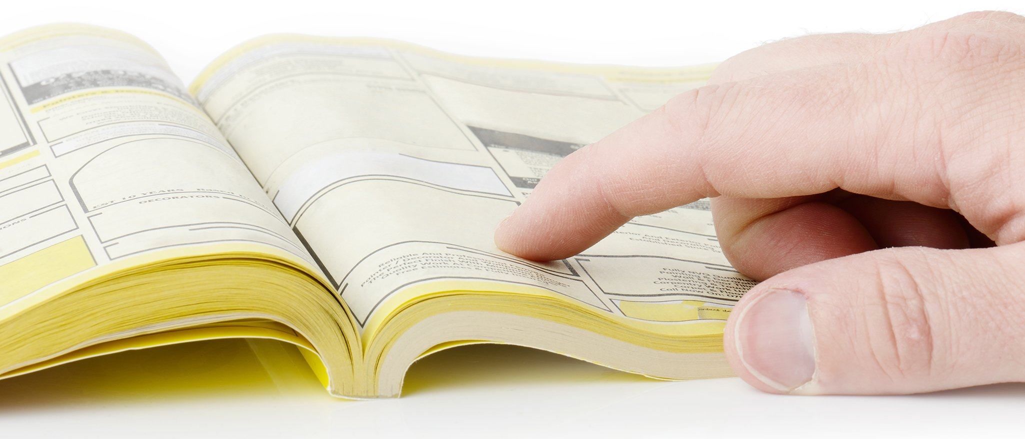 Customer-finds-number-in-yellow-pages-with-hand